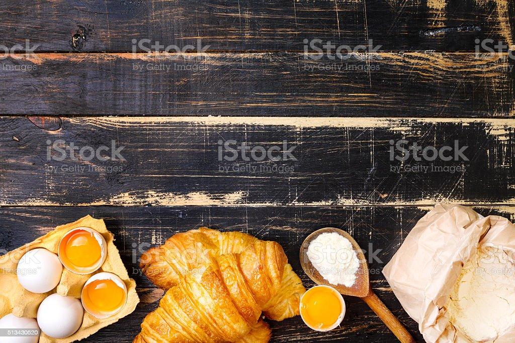 Croissants, flour, eggs, spoon background stock photo