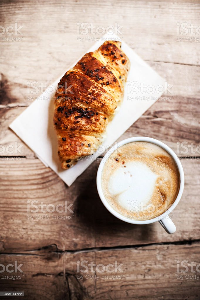 Croissants with coffee on wooden background stock photo