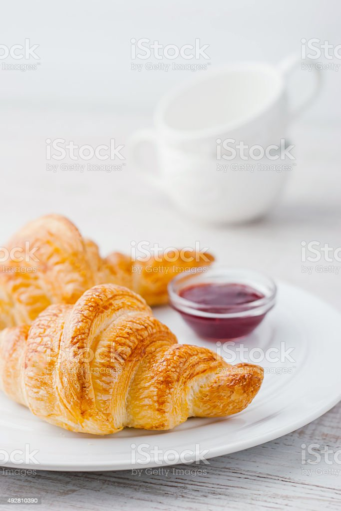 Croissants with jam and two white ceramic cups vertical stock photo