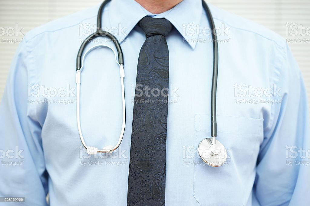 crop of physician  with stethoscope over blue shirt stock photo