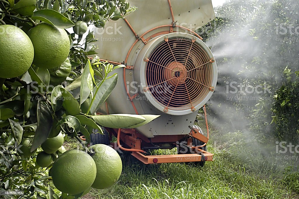 A crop sprayer on some fruit trees stock photo