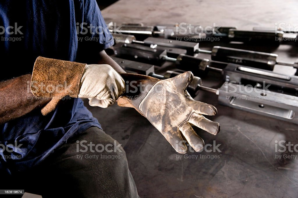 Cropped African American worker donning gloves royalty-free stock photo
