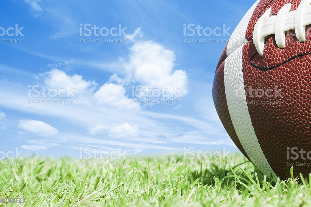 Cropped american football on green grass with blue sky royalty-free stock photo