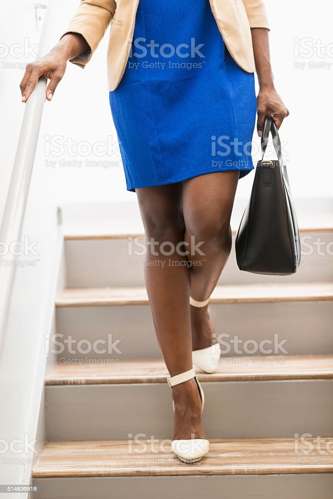 Cropped black woman with purse walking down stairs stock photo