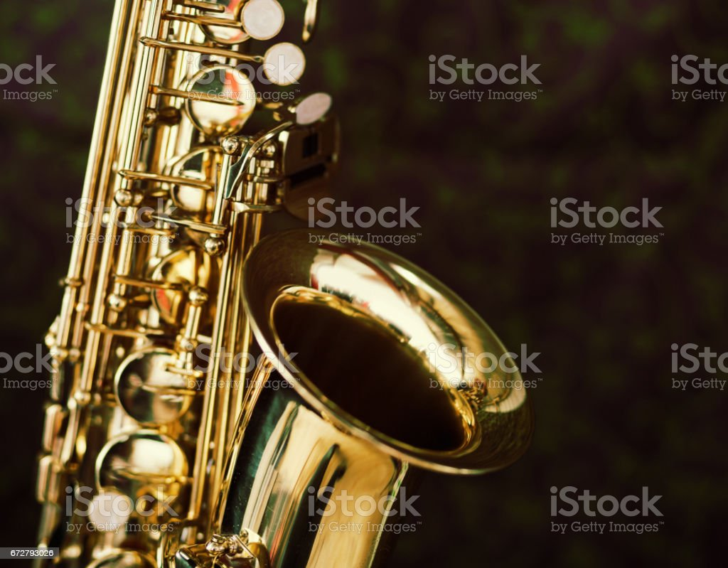 Cropped close up of gleaming golden saxophone on black stock photo