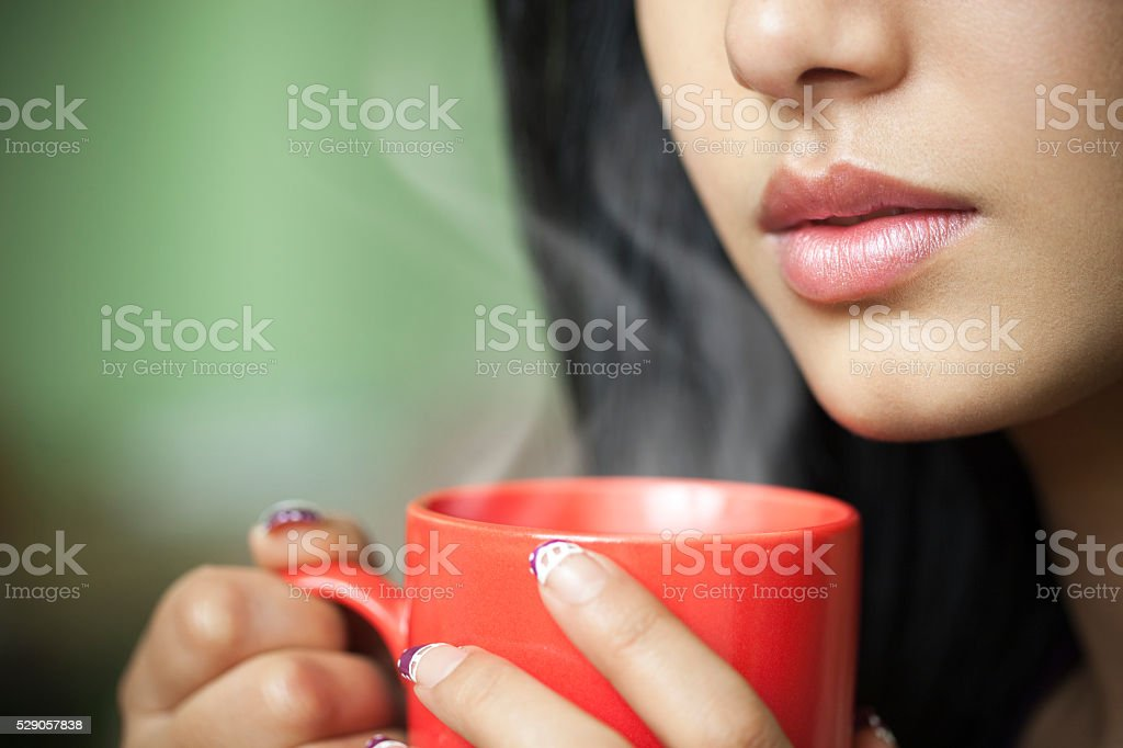 Cropped close-up of young woman with hot steaming coffee mug. stock photo