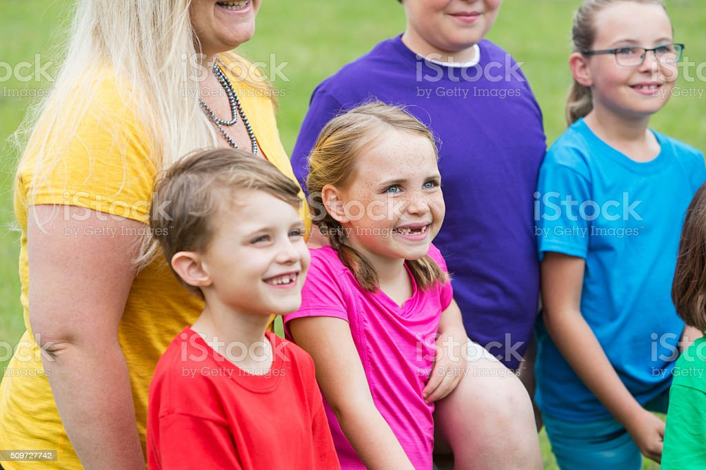 Cropped group of children and an adult outdoors stock photo