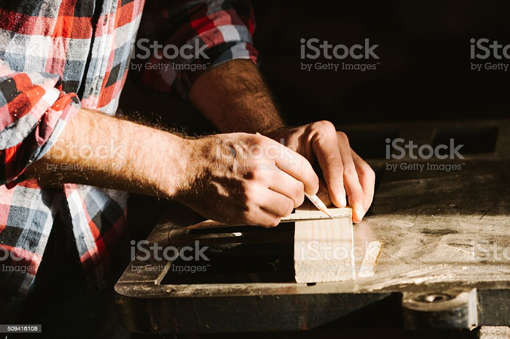 Cropped hand of a carpenter taking measurement of a plank royalty-free stock photo