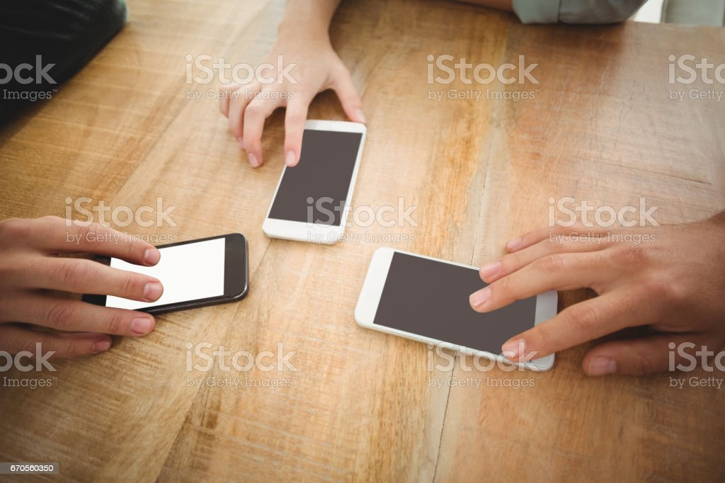 Cropped hands touching smartphones at office stock photo