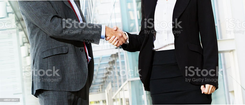 Cropped handshake between businessman and businesswoman; it's a deal! stock photo