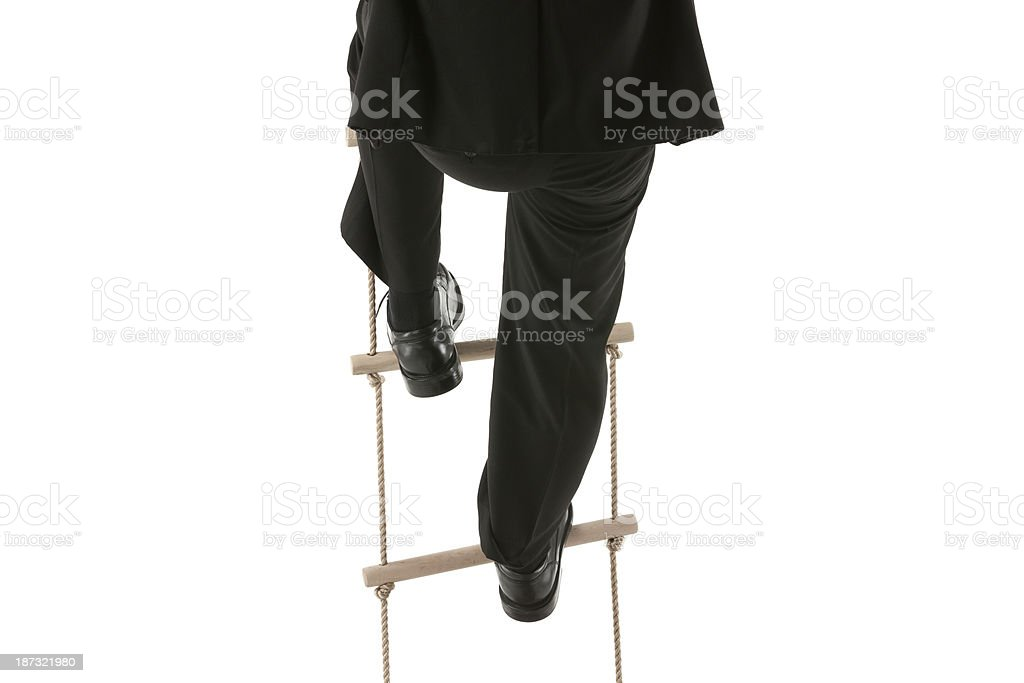 Cropped image of a businessman climbing rope ladder stock photo