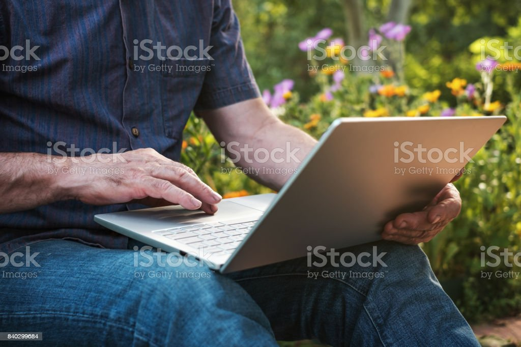 Cropped image of a mature man working on his laptop in garden, old male blogger typing on notebook stock photo