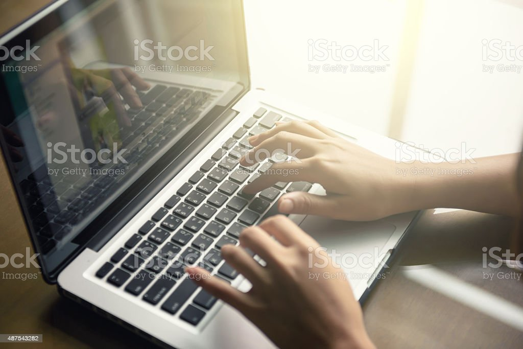 Cropped image of a woman working on  laptop stock photo