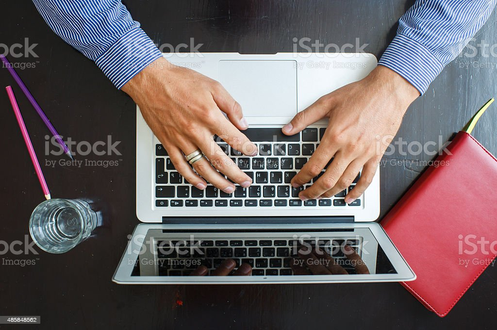 Cropped image of a young man working on his laptop stock photo