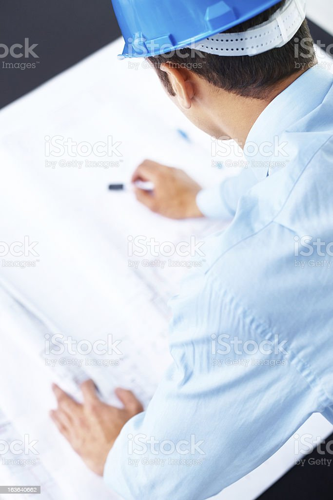 Cropped image of an architect working on blue prints royalty-free stock photo