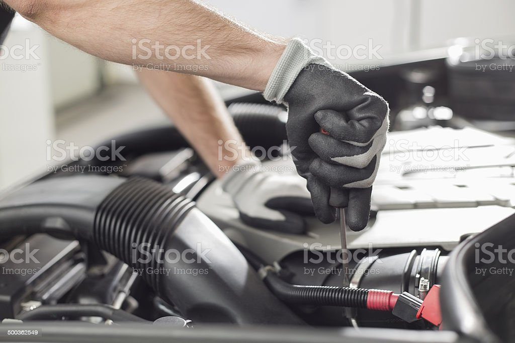 Cropped image of automobile mechanic repairing car stock photo