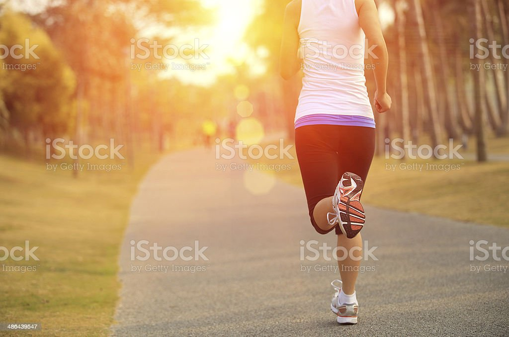 Cropped image of jogging woman, sun in background stock photo