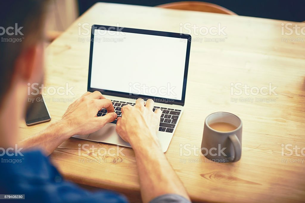 Cropped image of male blogger using laptop by coffee cup stock photo
