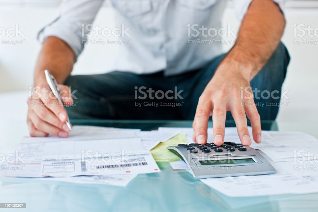 Cropped image of seated man using calculator stock photo