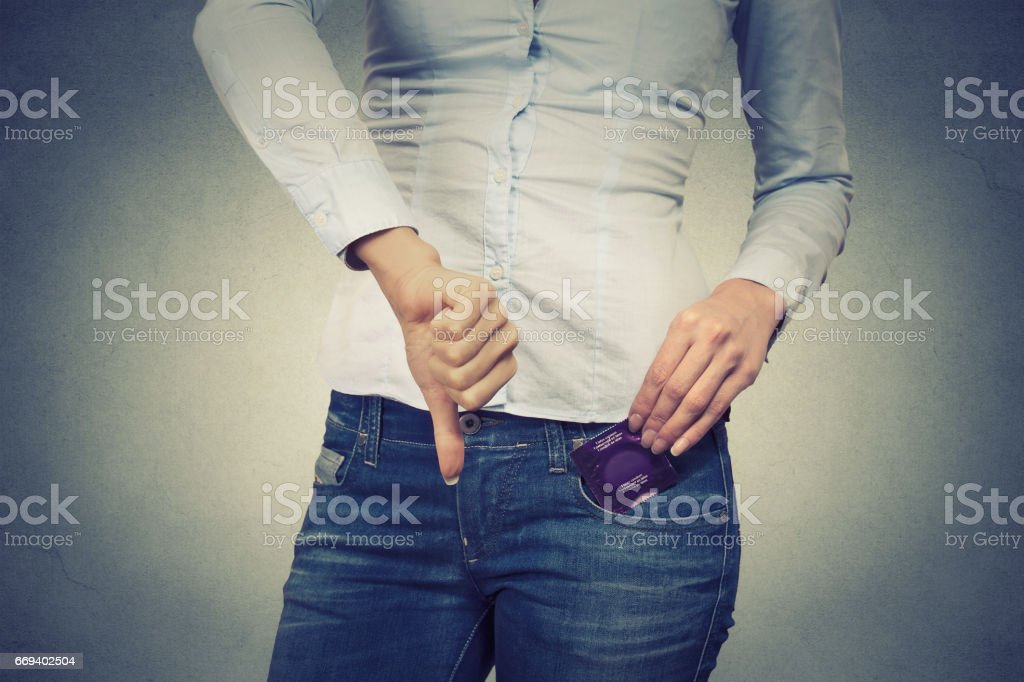 Cropped image woman with condom in her pocket giving thumbs down isolated on gray wall background stock photo