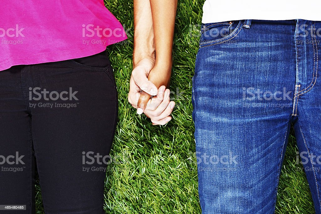 Cropped look at affectionately clasped hands of young couple stock photo
