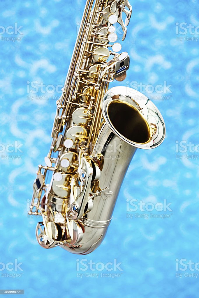 Cropped look at bell and keys of saxophone against blue royalty-free stock photo