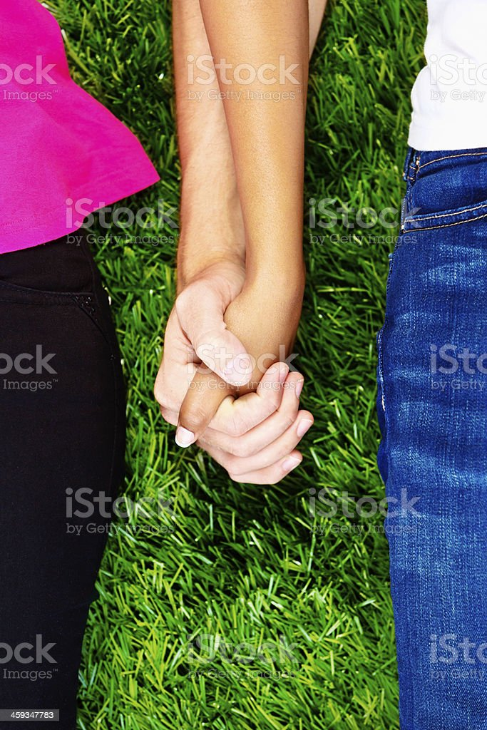 Cropped look at romance: hand-holding couple on grass stock photo