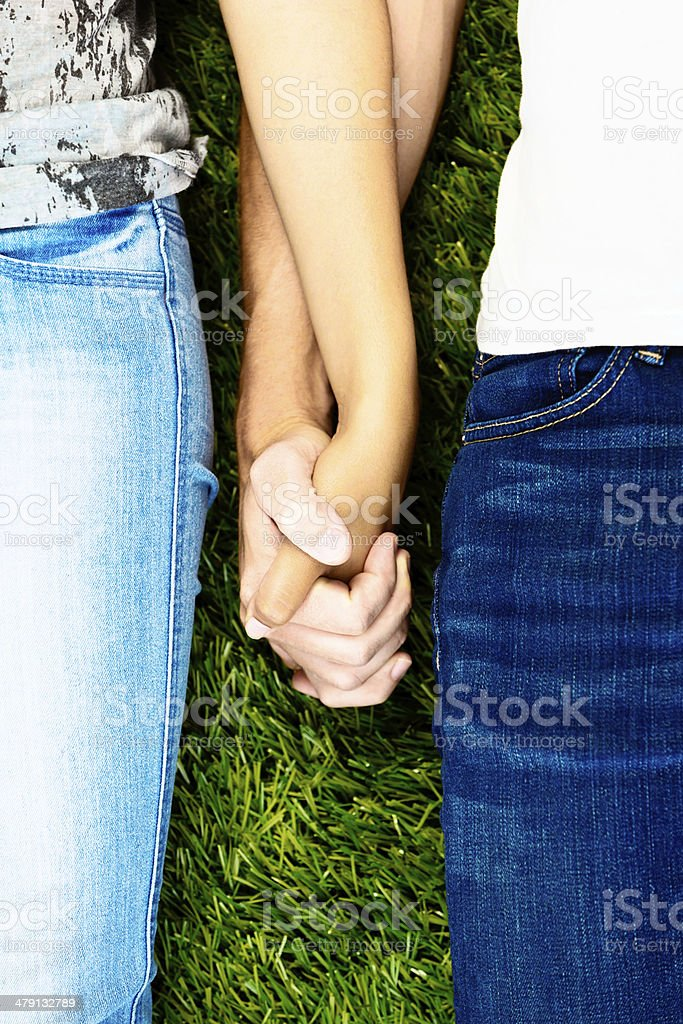 Cropped look at young couple holding hands against grass stock photo