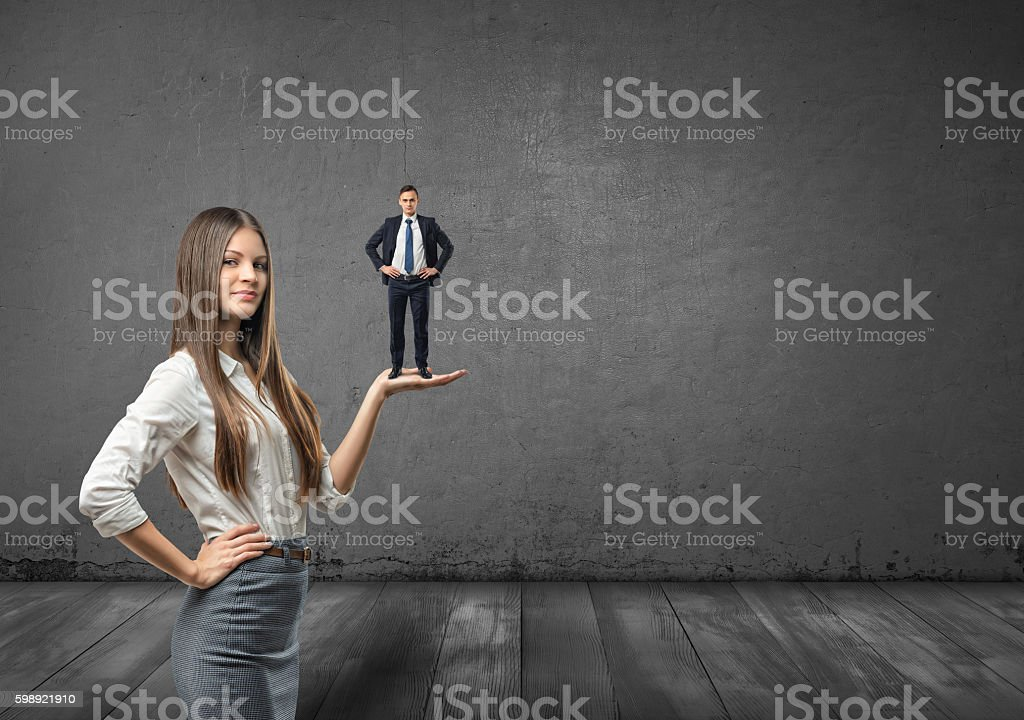 Cropped portrait of big businesswoman holding small businessman on her stock photo