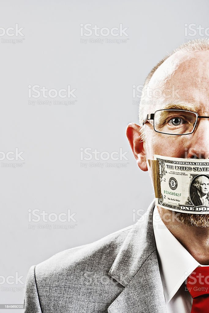 Cropped portrait of businessman silenced by dollar bill stock photo