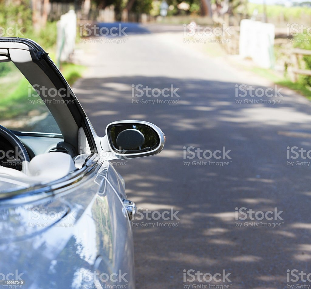 Cropped rearview of silver convertible on idyllic country road royalty-free stock photo