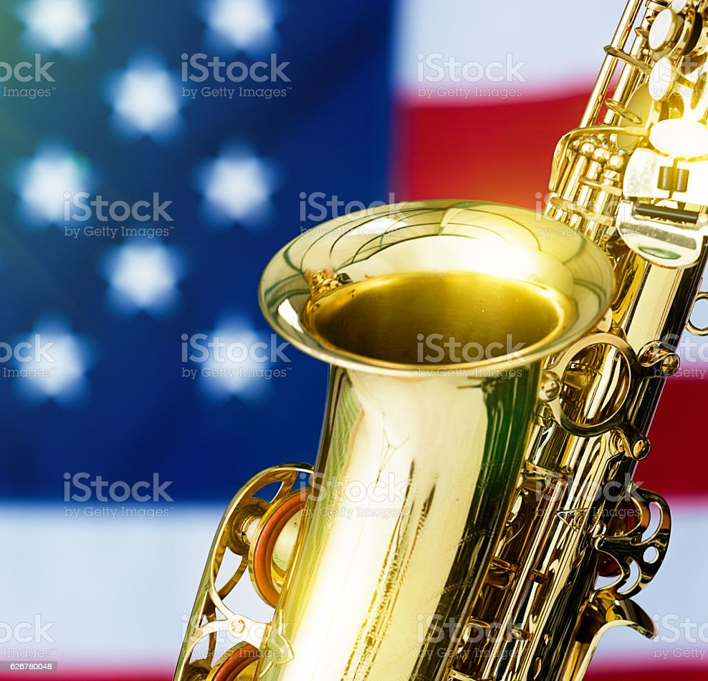 Cropped saxophone looking shiny in front of US national flag stock photo