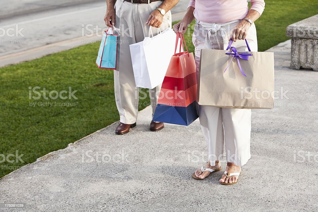 Cropped senior couple holding shopping bags stock photo