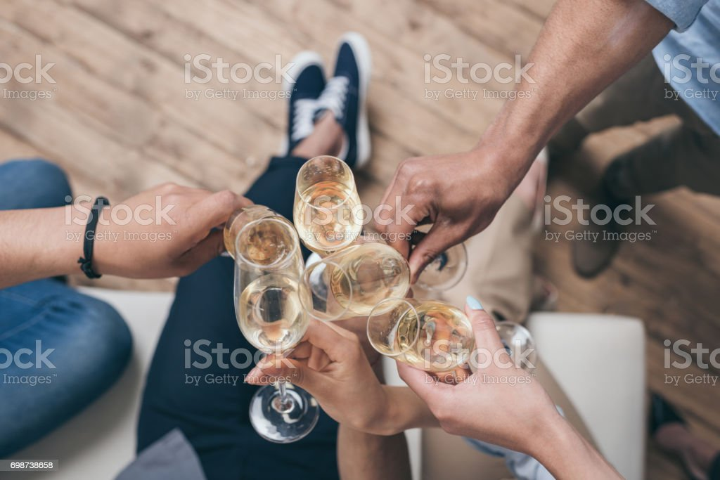 cropped shot of friends clinking with champagne glasses at home stock photo