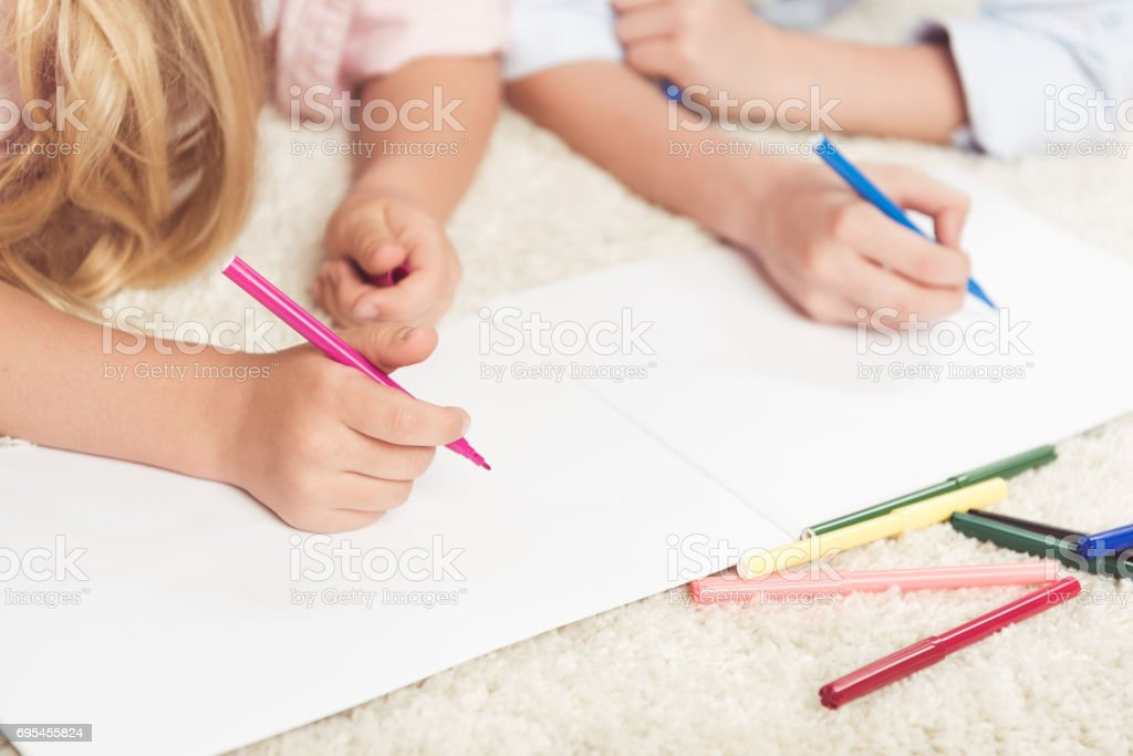 cropped shot of kids writing with felt pens on blank paper sheet at home stock photo
