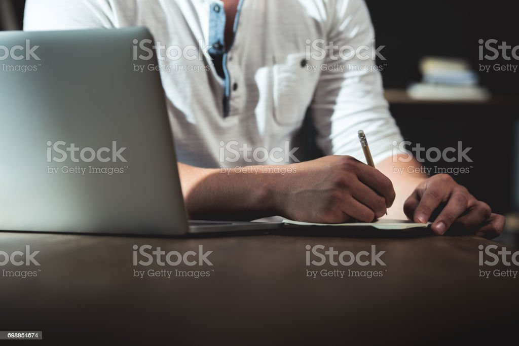 Cropped shot of man writing in notebook during work while sitting at the table with laptop stock photo