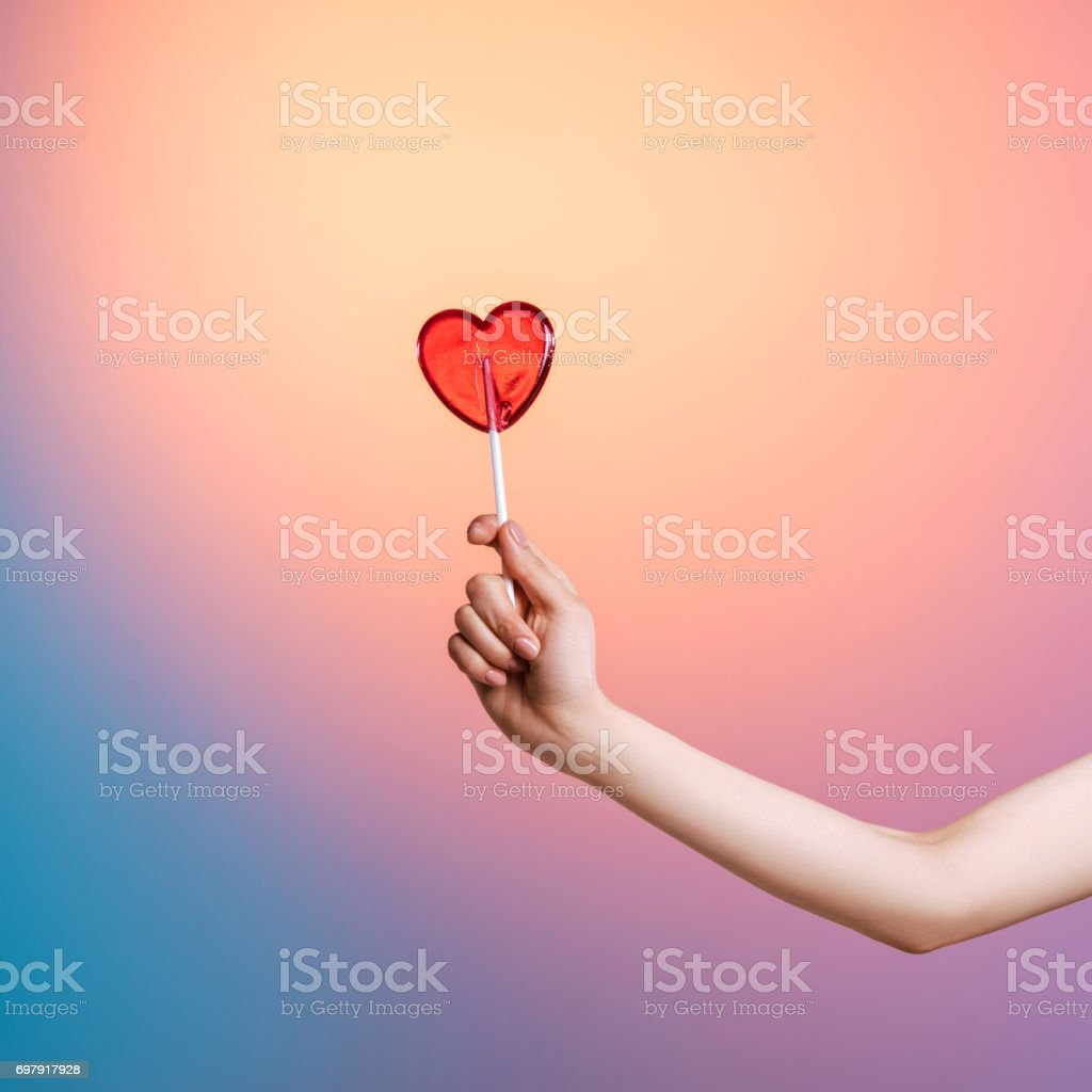 Cropped shot of person holding heart-shaped lollipop in studio stock photo