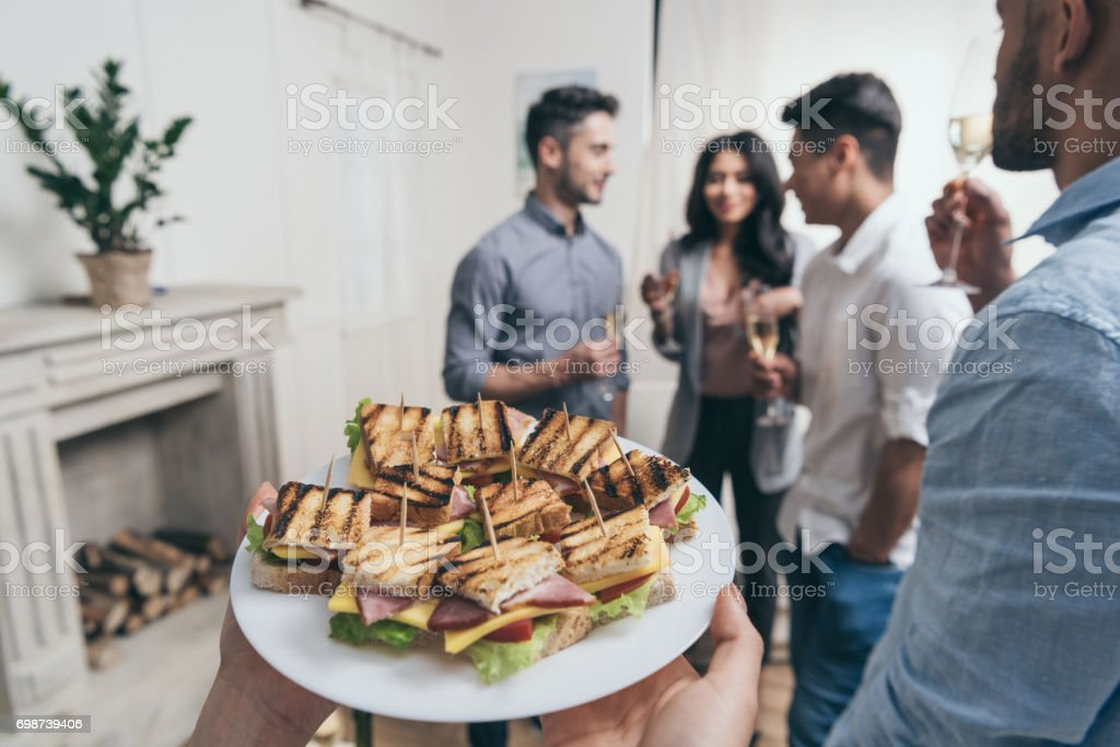 Cropped shot of person holding plate with tasty sandwiches while smiling young friends drinking champagne behind stock photo