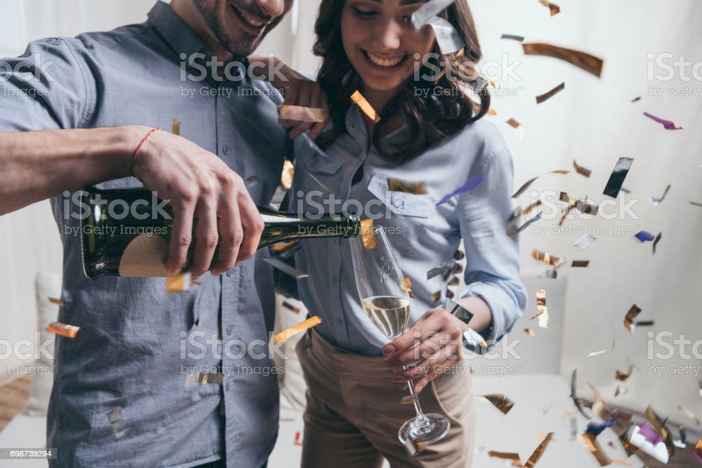 Cropped shot of smiling man pouring champagne to happy young woman at party stock photo