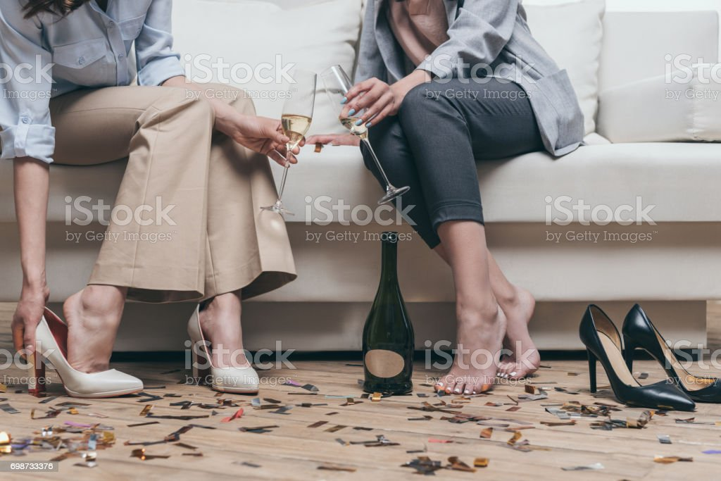 cropped shot of tired women drinking champagne while resting on sofa at home stock photo