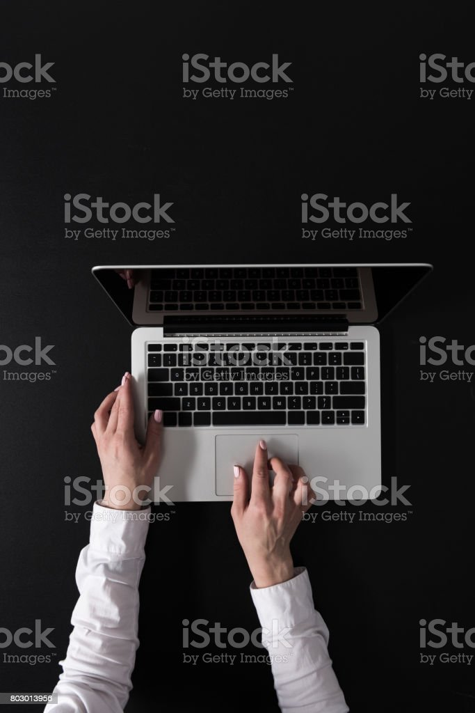 cropped shot of woman working on laptop isolated on black stock photo