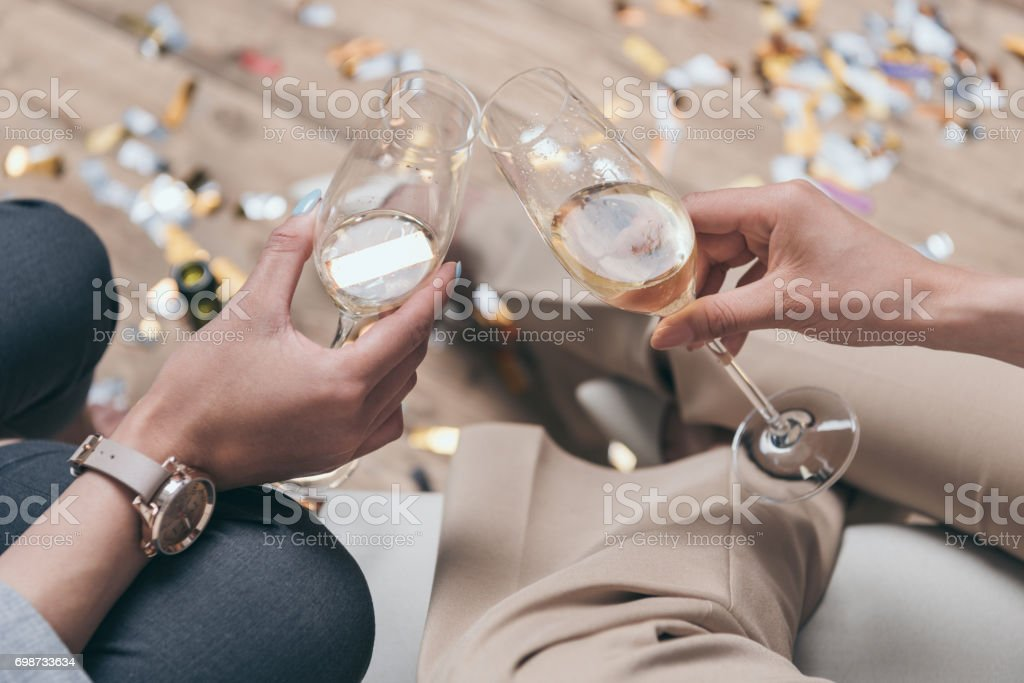 cropped shot of women celebrating and drinking champagne at home stock photo