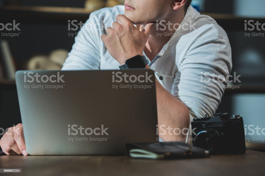 Cropped shot of young man being lost in thought during work on laptop stock photo