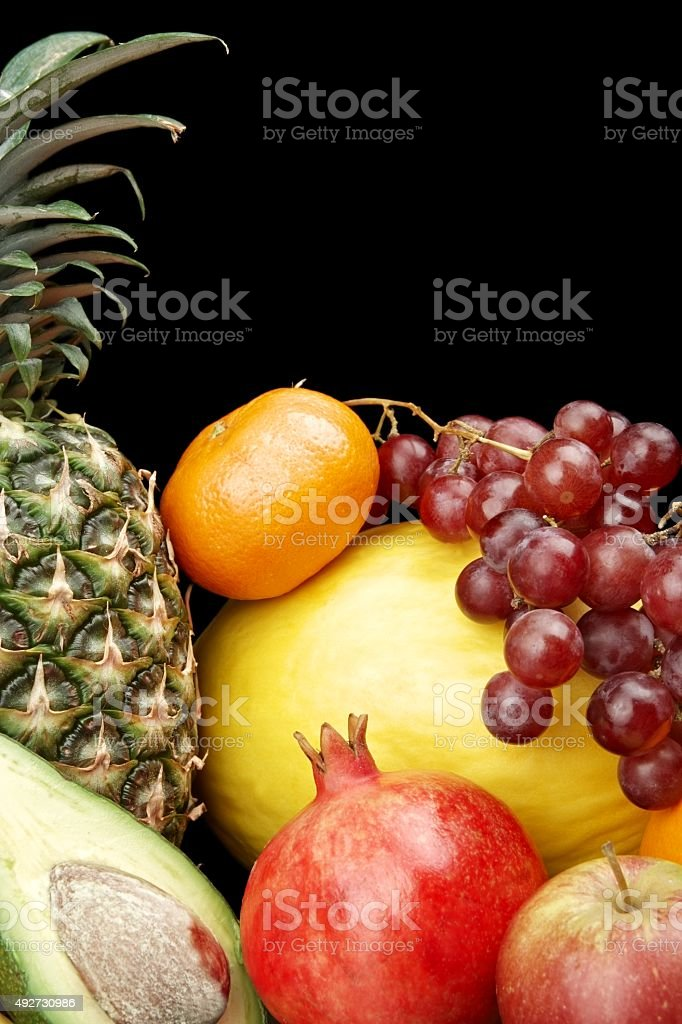 Cropped vertical view many colorful fruits on black with reflection stock photo