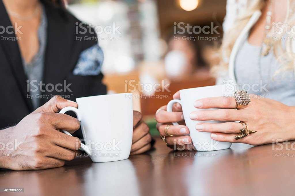 Cropped view of a couple having coffee in restaurant stock photo