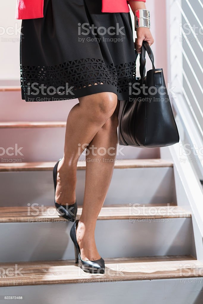 Cropped view of black woman walking down stairs stock photo