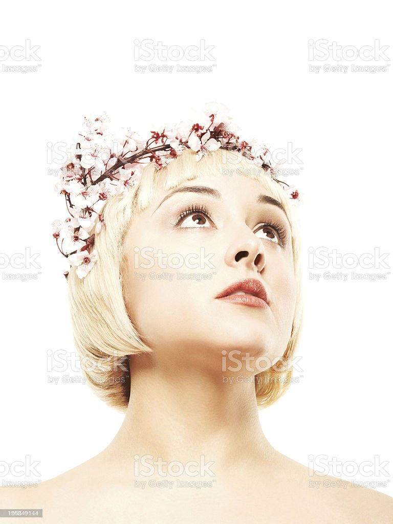 Cropped view of blonde looking up wearing pink flower wreath stock photo