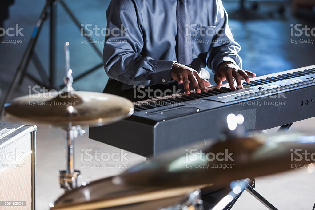 Cropped view of man playing keyboard in band stock photo