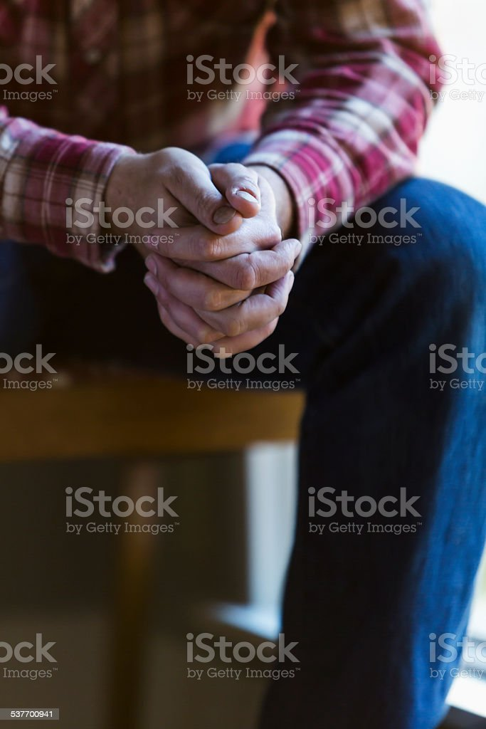 Cropped view of man sitting with hands clasped stock photo