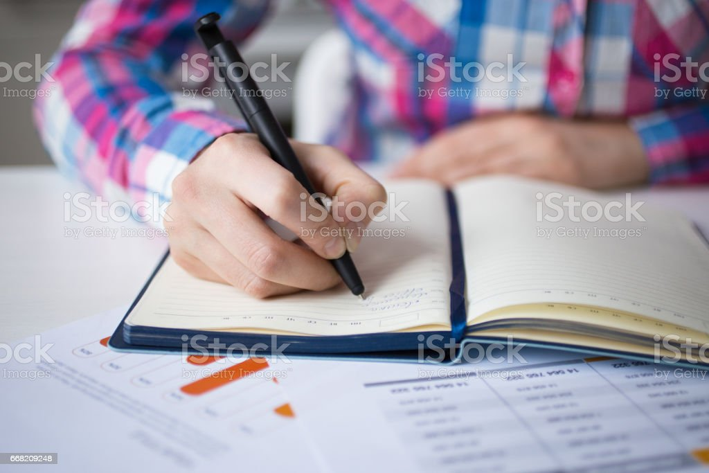 Cropped View of Manager Making Notes in Diary stock photo
